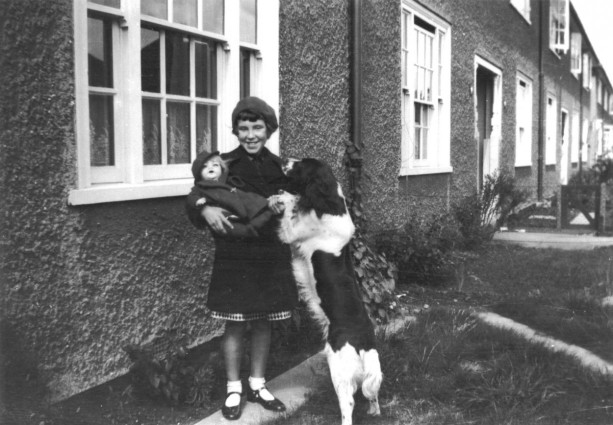 Len with her dolly and Hector, the family dog. Taken outside the new rented home in Dagenham, Essex