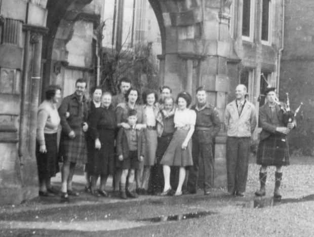 """Group at Auchendrennan New Year's Day, 1947. Dad and Mum at left and right. Mrs Mac is in Centre with Henry Lindsay at her back - that's Henry's brother in kilt next to me. The piper appeared playing a tune, he had walked all the way from Tarbert after playing all night!"" Mums annotation on back of photo."